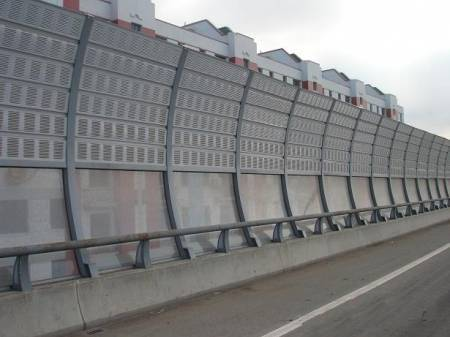 A freeway sound barrier with aluminum panel at the top and polycarbonate sheet at the bottom.