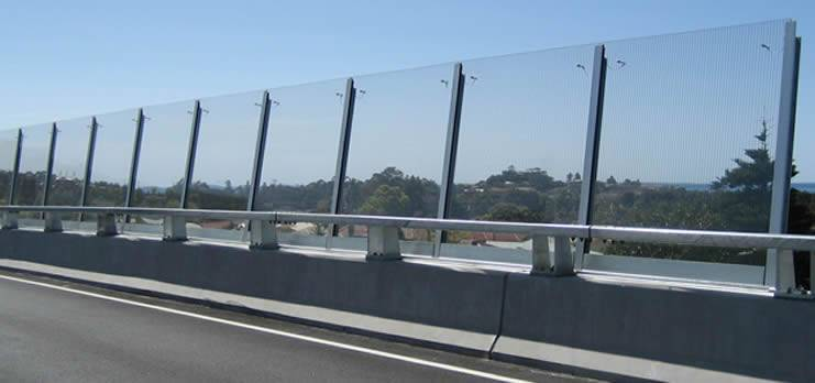 Acrylic sound barrier installed along a highway which crosses the residential area.