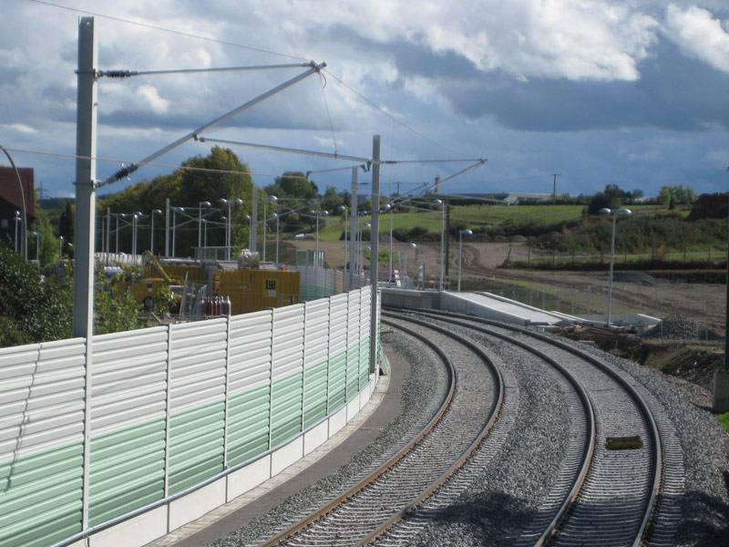 Green and white PVC reflective sound barrier separating railway from residential area.