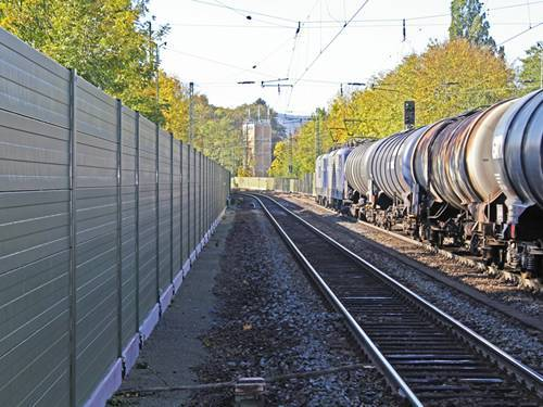 Aluminum sound barrier along a railway reflects unwanted noise toward the resource.